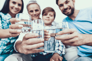 Smiling Family Drinking Water in Glasses at Home.