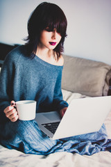 Portrait of a young caucasian woman with of coffee or tea and notebook at home