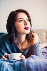 Portrait of a young caucasian woman with of coffee or tea at home