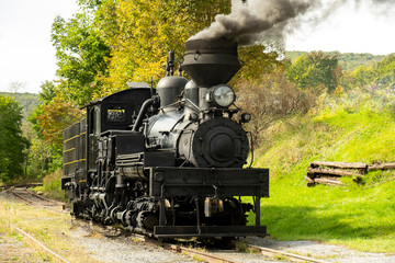 Old steam locomotive sitting on the railroad tracks in color