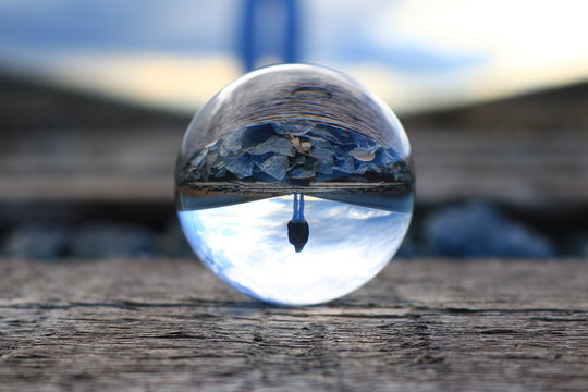 Refection of a woman walking on the train tracks in a lens ball