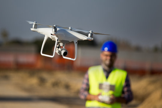 Construction worker with drone at building site
