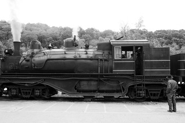 Amish man looking at a steam locomotive at the train station in black and white
