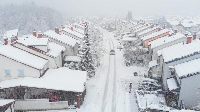 AERIAL: Car drives down the snowy road leading through the suburban neighborhood