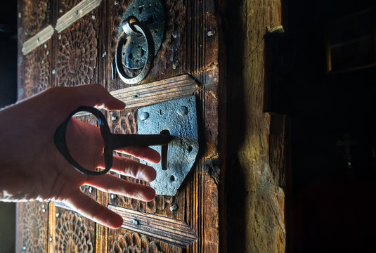 Hand unlocking rustic door of wooden church with a big key