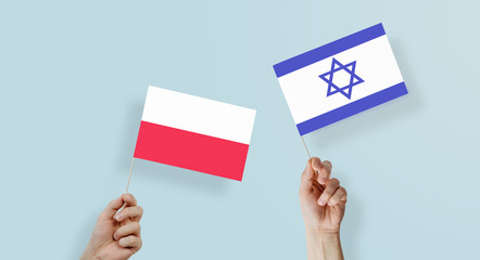 Hands are holding the flags of Poland and Israel. The concept of establishing relations between Poland and Israel. Jewish relations with Poland. Concentration camp, the fight against the Nazis.