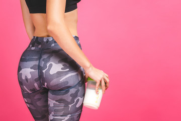 Attractive beautiful sporty young woman with protein shake bottle isolated over pink background. Close-up.