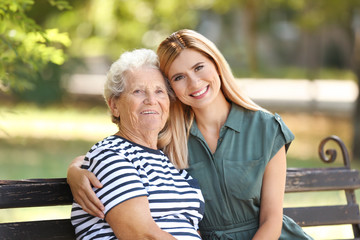 Woman with elderly mother on bench in park
