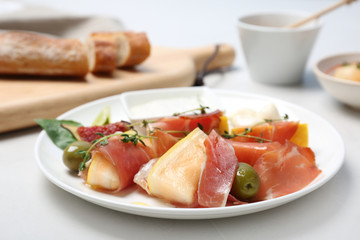 Plate with melon and prosciutto appetizer on light table