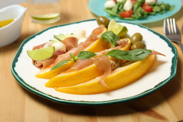 Plate with melon and prosciutto appetizer on wooden table