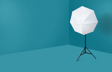 A white umbrella on a photographic stand in a blue room. The concept of photographic equipment, setting photo equipment in a photo studio, taking photos. Correct lighting.