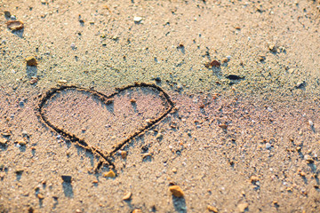 a heart in the sand on the beach.heart drawn on sand. horizontal composition.