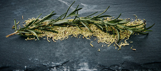 A sprig of fresh green rosemary placed on dried rosemary on a dark stone counter top. Food concept and seasoning dishes. Strengthening the taste with herbs, improving the taste.