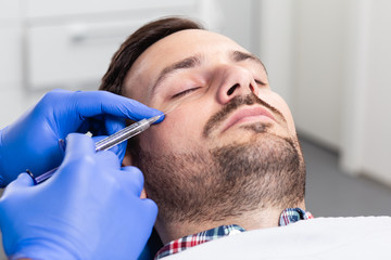 Handsome man is getting a rejuvenating facial injections. He is sitting calmly at clinic. The expert beautician is filling male wrinkles by hyaluronic acid.