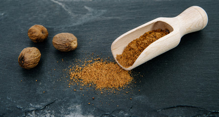 Fototapeta Ground nutmeg on a dark, stone top and whole nutmeg nut seeds. Powder nutmeg on a wooden bucket. The concept of using herbs and spices for dishes. Improving the taste. obraz