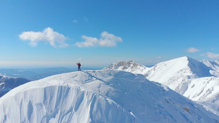 AERIAL: Spectacular sunny mountain range surrounds skier taking photos of nature