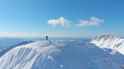 AERIAL: Unrecognizable skier taking photos after reaching peak of snowy mountain