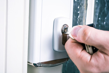 Male Hand Using A Key With A Security Door Lock, Prevent Burglary Concept