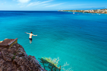 Man jumping off a cliff, Westpunt, Curacao, Netherlands. Copy space for text. Wall mural