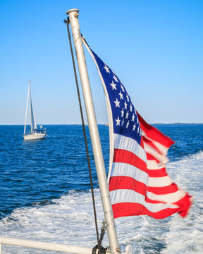 An American flag whips behind a speed boat creating a white wake on blue water. A sail boat is behind and to the right of the speed boat. A blue sky is the background.