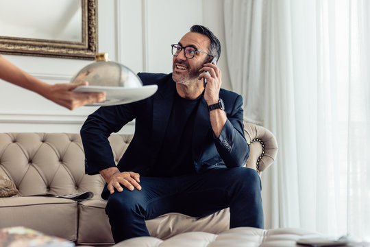 Waiter serving food to businessman in hotel room