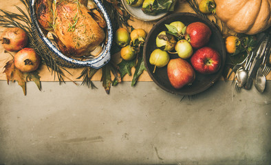 Thanksgiving dinner table. Flat-lay of roasted chicken or turkey, fruit, pumpkin, cutlery, leaves over yellow table runner on grey concrete background, top view, copy space, horizontal composition