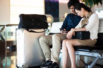 空港の待合室でスマートフォンを眺めているカップル