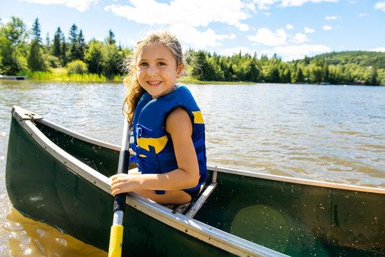 Happy kid enjoying canoe ride on beautiful river