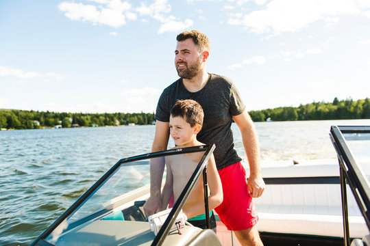 Man driving boat on holiday with his son kid