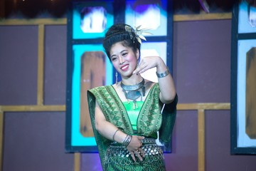 The lady in Middle Thai classical dancing suit is showing pattern of traditional dancing on platform.