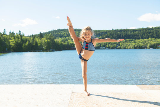 cute little girl doing some stretching close to a lake