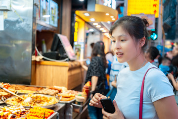 Girl trying Hong Kong local street food - curry fish balls