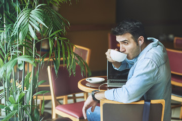 Attractive young man enjoying cup of cappuccino in coffeeshop