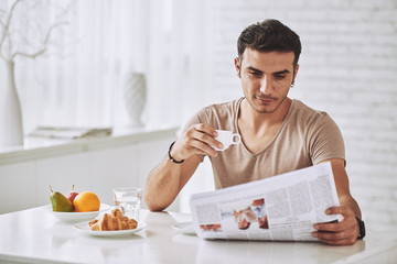 Young man enjoying breakfast and reading newspaper