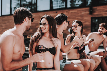 Young Smiling Friends Drinking Wine at Poolside