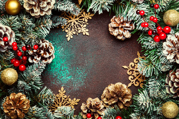 Christmas or New Year frame composition with  green snow fir branches, pine cones, golden snowflakes, Christmas balls, red berries, and alarm clock on brown background, top view