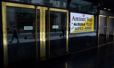 People are seen reflected as they walk past an out-of-business store in Buenos Aires' financial district