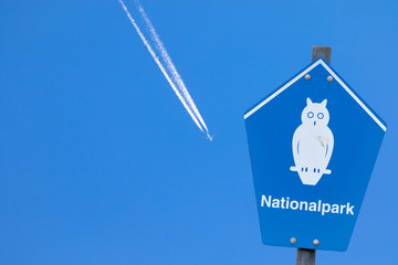"Blue sign of a national park beside a contrail at the blue sky with german lettering ""nationalpark"" means national parc"