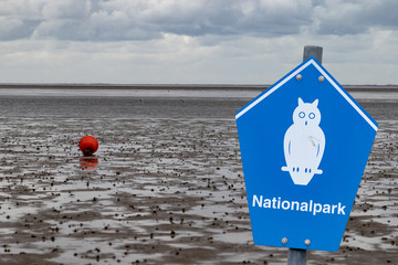 "Blue sign of a german national park in front of wadden with german lettering ""nationalpark"" means national parc"