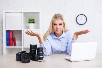 female photographer with camera, computer and photography equipment having no idea