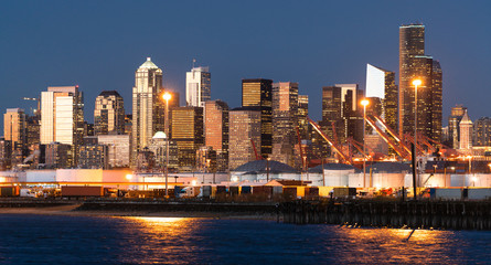 The Seattle Washington waterfront glows at dusk showing tanks and shipping containers at the port