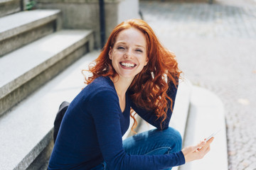 Young smiling woman sitting on steps with phone
