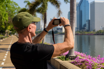 Senior tourist man wearing cap while taking pictures at peaceful