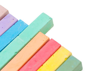 Colored chalks over a white background close up