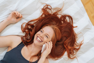 Young woman chatting on her mobile lying in bed