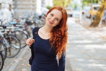 Friendly young redhead woman wearing a backpack