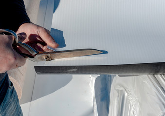 Worker with a a scissor cuts  PVC sheets for waterproofing a terrace. Selective focus