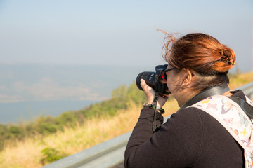 traveler backpack take photograph by dslr camera,landscape of green tea fields. holidays activity.