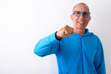 Studio shot of happy bald senior man smiling while wearing eyegl
