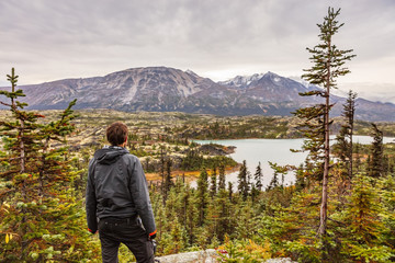Alaska hiking man travel outdoor lifestyle, Young traveler hiker at mountains landscape in autumn.